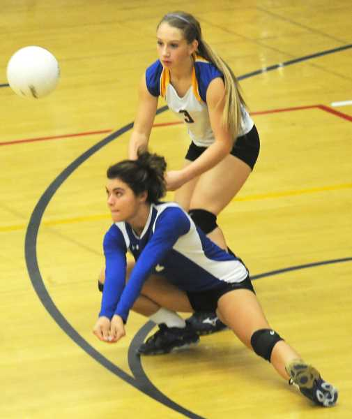 by: LON AUSTIN/CENTRAL OREGONIAN - Laken Berlin passes the ball while Aspen Christiansen backs her up during the second set of the Cowgirls victory over the Bend Lava Bears Tuesday Night.