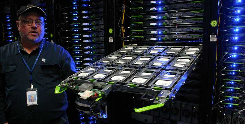 by: JASON CHANEY - Facebook data center site director Chuck Goolsbee displays a collection of four terabyte drives used in the cold data storage server racks.