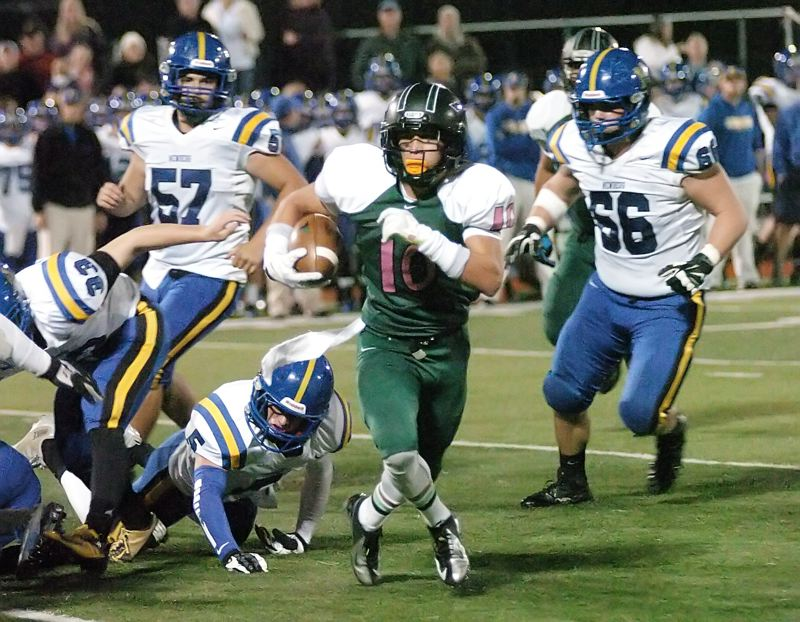 by: DAN BROOD - ON THE RUN -- Tigard senior Manu Rasmussen heads up field in Friday's game. Rasmussen rushed for 208 yards and four touchdowns in the 63-21 win over Newberg.