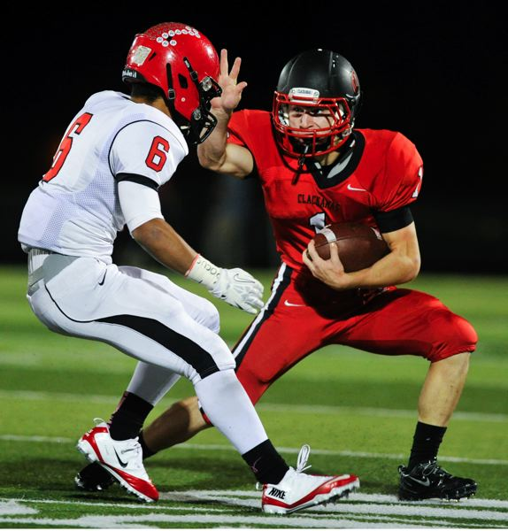 by: JOHN LARIVIERE - Oregon City sophomore defensive back Trevon Bradford (6) holds Clackamas senior running back Dan Sherrell to a short gain in Fridays game at Clackamas.