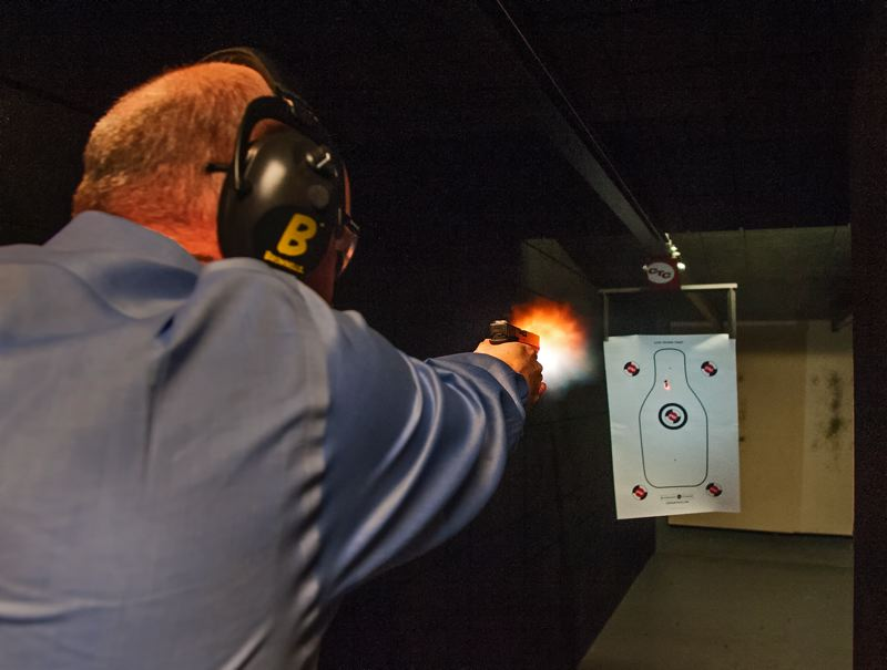 by: SPOKESMAN PHOTO: JOSH KULLA - Crimson Trace President Lane Tobiassen uses one of his companys laser sights (red dot visible on target) to fire a Glock G17 9mm pistol in the companys indoor shooting range.