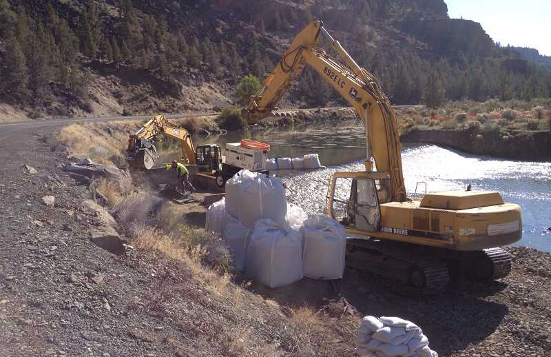 by: BILL MINTIENS - Crews place a gas-powered generator that will be used as part of the dam removal project.