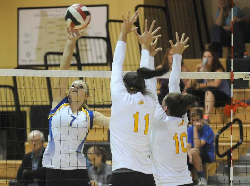 by: LON AUSTIN/CENTRAL OREGONIAN - Hannah Troutman tips the ball over a double block by the Central Catholic Rams during the West Linn Invitational Volleyball Tournament. Crook County was narrowly edged by Central Catholic in the semifinals of the tournament. The Rams went on to edge Jesuit for the tournament championship.