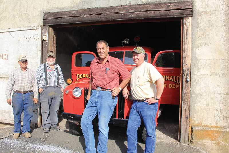 by: FILE PHOTO - Four members of the Donald Community Association (From left) - Rick Zacher, Frank Stormo, Walter Pohlschneider and Todd Deaton, are being sued to return dozens of assets, including this 1944 Ford fire truck.