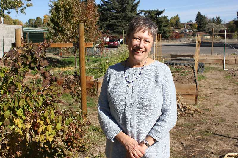 Pastor Jan Kozak stands in the Margaret Dement Garden of Eatin', which the church operates. Hundreds of pounds of produce is donated to local food programs each year.