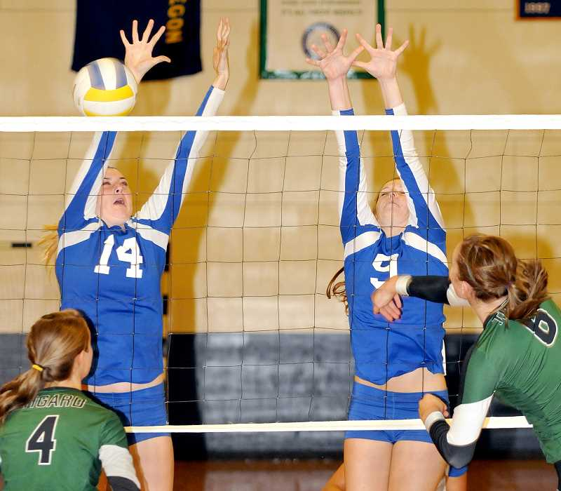 by: SETH GORDON - First line of defense -- Cheyenne Cochrane and Emma Voss rise for a block during Newberg's 3-0 win over Tigard Oct. 17 at McGrath Gymnasium. The Tigers clinched the Pacific Conference title with the victory and as the No. 5-ranked team in the OSAA power rankings, should play at home for the first two rounds of the upcoming 6A state playoffs.
