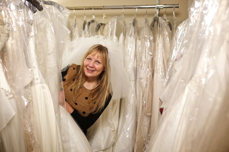 by: TRIBUNE PHOTO: JAIME VALDEZ - Jan Schumacher plays Peekaboo in between a row of bridal gowns in her  which has 300 dresses alone stored there. Schumacher who operated one of Portlands biggest bridal stores, has over 1000 bridal dresses stored at her house that she sells reasonably.