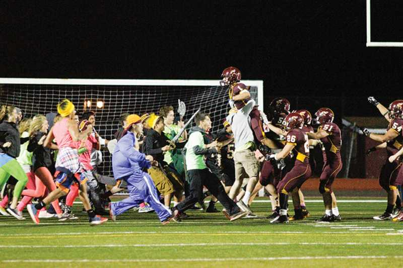 by: NEWS-TIMES PHOTO: AMANDA MILES - Forest Grove students rush the field and hoist receiver Ethan Thursam into the air following Friday's 31-16 homecoming victory against Hilhi.
