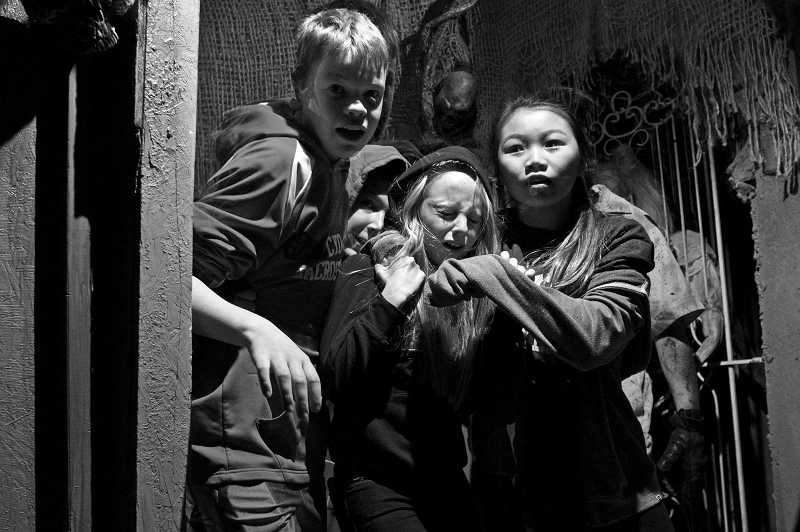 by: TIMES PHOTO: JAIME VALDEZ - Valley Catholic Middle School eighth-graders Angus Johnson, Tyler Wahl, Erin Connelly and Chloe Golik anxiously walk around a corner to the next room at the 13th Door Haunted House on Southwest Murray Boulevard.