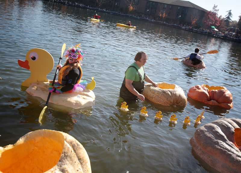 by: TIMES PHOTO: JONATHAN HOUSE - Charity Marshall laughs along with friends and family as she rides the pumpkin duck during the West Coast Giant Pumpkin Regatta on Saturday.