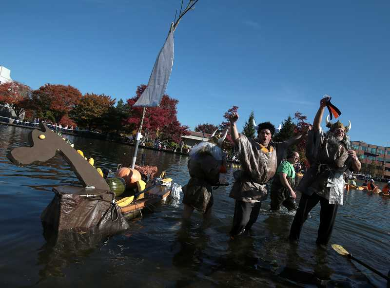 by: TIMES PHOTO: JONATHAN HOUSE - From left, Jack LaRue and Ron Barker celebrate winning Best Costume for the viking ship during the West Coast Giant Pumpkin Regatta.