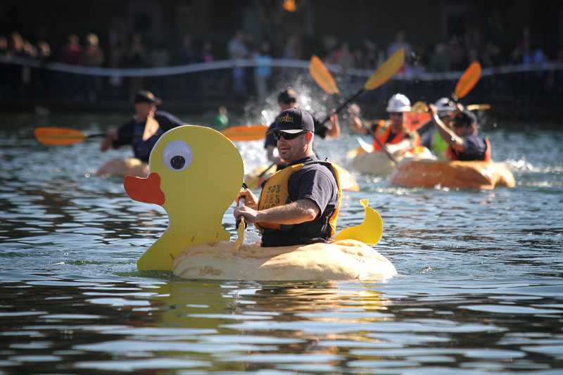 by: TIMES PHOTO: JONATHAN HOUSE - Tualatin Valley Fire & Rescue's James Smario leads his capture the flag team against the Army Corps of Engineers for another win at the West Coast Giant Pumpkin Regatta.