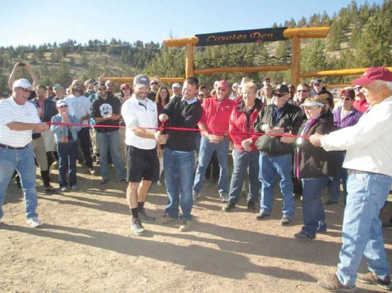 by: JOHN BOWLER - Crooked River Ranch disc golf course designer Sean Remer, right center, cuts the ribbon at the course on Saturday, with Jim Tobish, who assisted with the course. Holding the ribbon are Ranch Club and Maintenance Association board members Mitch Poppert, left, and Vene Dunham, right.