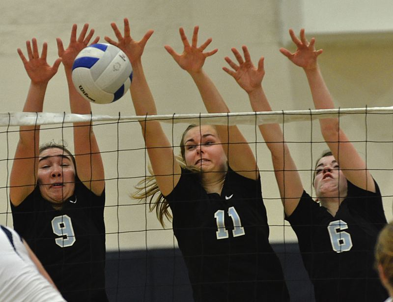 by: VERN UYETAKE - Lakeridge's Malia Scott, Maddie Marshall and Kacie Van Stiphout go up for a block during last week's match against Lake Oswego.
