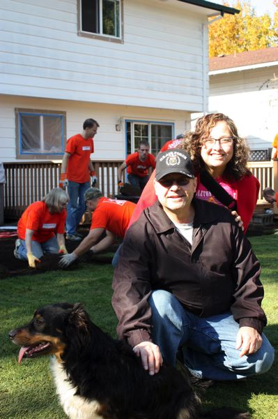 by: HILLSBORO TRIBUNE PHOTO: DOUG BURKHARDT - Chuck Reynolds and his wife Stephanie enjoy their new backyard with their dog, Buddy, while volunteers work behind them.