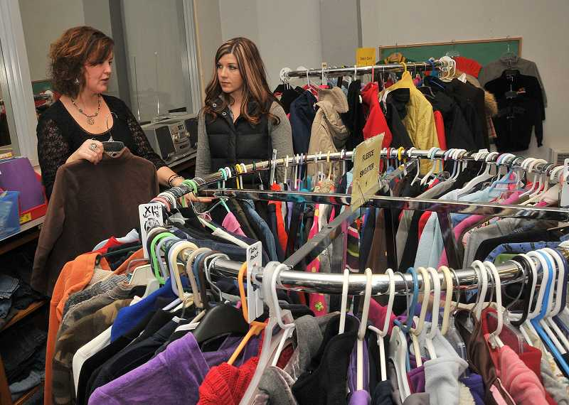 by: PAMPLIN MEDIA GROUP: VERN UYETAKE - Suzanne Dove, PTA leader for the Clackamas County Clothes Closet, consults with volunteer Rachel Thompson.