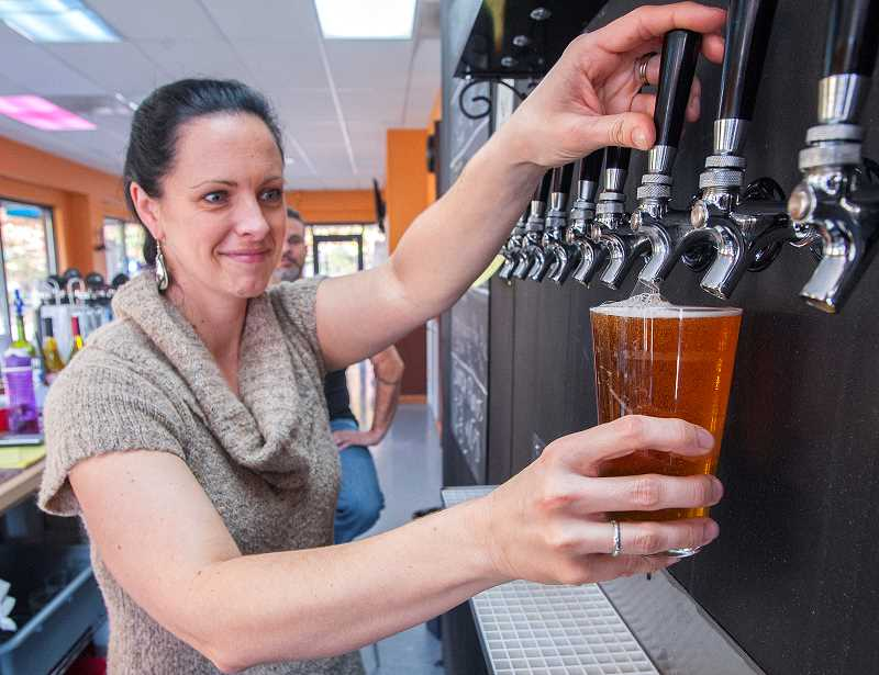by:  JOSH KULLA - Erin Telles, a bartender by profession, pulls a pint at The Beer Station, Wilsonville's newest craft brewing emporium.