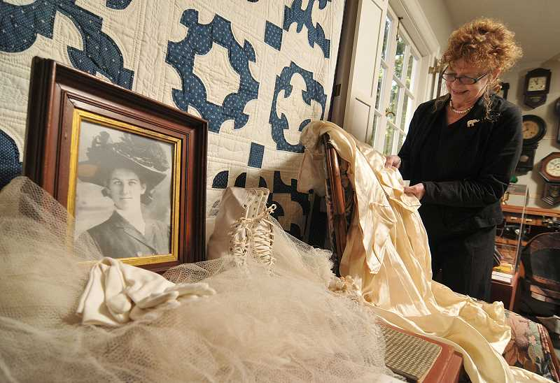 by: VERN UYETAKE - Jude Graham looks over items highlighting the legacy of Lucy Pollard this Halloween season at the Oswego Heritage House, where her sad story lives on along with a quilt, a dress and other belongings.