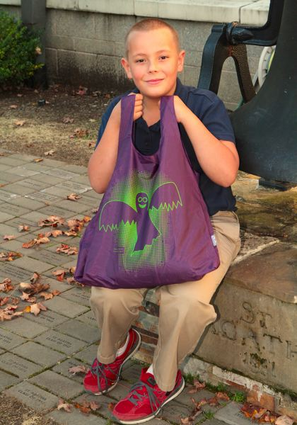 by: DAVID F. ASHTON - St. Agatha Catholic School third grade student Theo Pashley shows the Halloween-themed bag he designed that sold out worldwide.