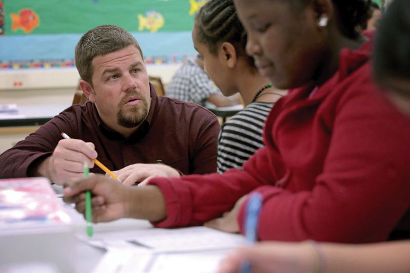 by: TRIBUNE PHOTO: JONATHAN HOUSE - George Middle School Principal Ben Keefer works with students as he fills in to teach an English Language Development class.