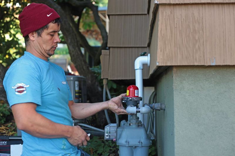 by: TRIBUNE PHOTO: JONATHAN HOUSE - Nick Perez of Earthquake Tech installs an automatic shutoff valve at a home in Southwest Portland.