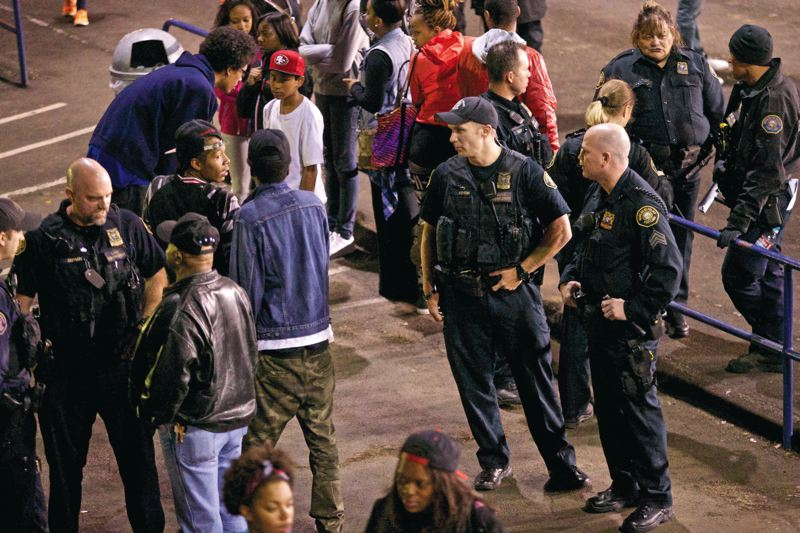 by: TRIBUNE PHOTO: JAIME VALDEZ - About three out of four homicides are the result of an argument between acquaintances that escalates. Police tactics to reduce homicides involves keeping apart people who might get into conflicts in the first place. In Portland, that means patrolling inside and outside Jefferson High School during football games. Here, Portland Police Gang Enforcement Officers Jim DeFrain, Charlie Asheim and sergeant Don Livingston watch for gang members in the milling crowd inside Jefferson's stadium.