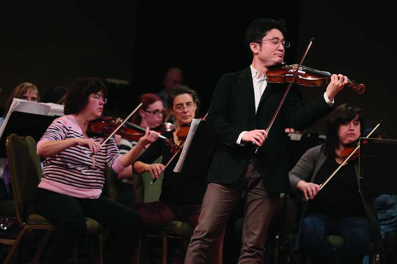 by: TIMES PHOTO: JONATHAN HOUSE - Japanese visiting violinist Kunito Nishitani rehearses a challenging piece he selected with the Beaverton Symphony Orchestra.