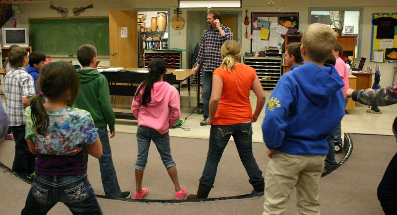 by: JASON CHANEY - Miss Powers' fourth grade Cecil Sly Elementary class dances with elementary music teacher Phil White. The school district added the music teacher position this year as part of an ongoing effort to restore programs cut during the recession.