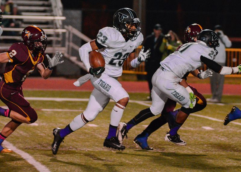 by: CHASE ALLGOOD, PAMPLIN MEDIA GROUP - INTO THE CLEAR -- Tigard junior running back Landon Floyd finds an opening during Friday's game at Forest Grove.