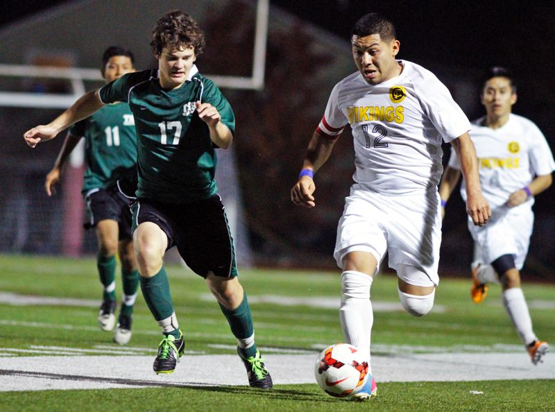 by: AMANDA MILES: PAMPLIN MEDIA GROUP - RACING -- Tigard senior Mick Whitehead (left) looks to get the ball away from Forest Grove's Reggie Lopez in last week's match.