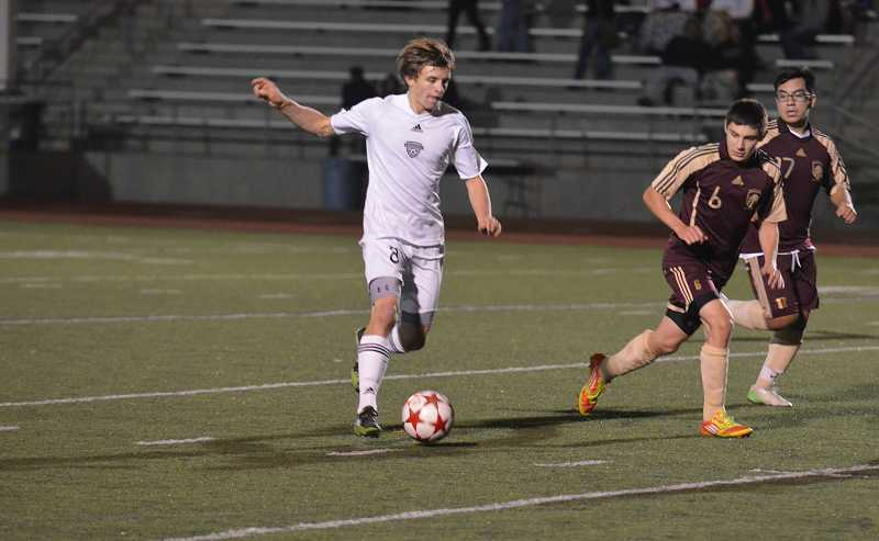 by: JEFF GOODMAN - Junior midfielder Jason Johnson (left) advances the ball Oct. 29 at Randall Stadium. The Wilsonville boys soccer team clinched a league title with a dominant rout of Milwaukie.