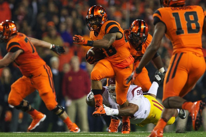by: TRIBUNE PHOTO: JAIME VALDEZ - Oregon State's Terron Ward runs through the arms of USC defensive tackle Joey Augello in the second half Friday night at Reser Stadium.