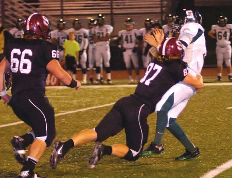 by: SANDY POST: PARKER LEE - Sandys Andrew Spencer crashes into the Summit quarterback as he releases the ball Friday night.