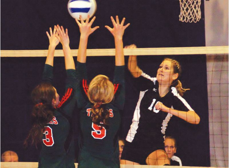 by: THE OUTLOOK: PARKER LEE - Portland Lutherans Kaitlin Howard pounds down a kill over two blockers during Saturdays second-round playoff win.