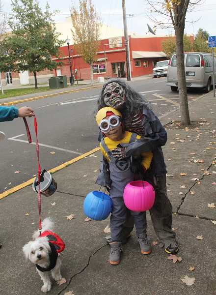 "by: JEFF MCDONALD  - A minion from ""Despicable Me,"" a zombie and their dog, the ladybug, celebrate Halloween in downtown Woodburn."