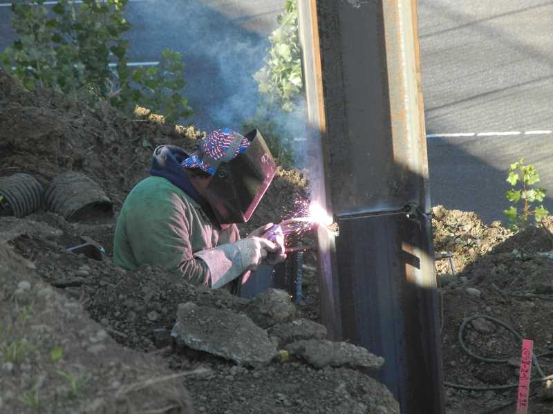 by: JEFF MCDONALD  - A K&E Excavation Inc. worker welds the foundation of a bridge footing as part of the Woodburn Interchange Project. The bridge will double in size when completed next year.