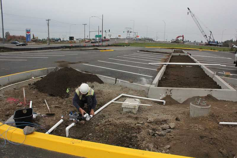 by: JEFF MCDONALD  - A worker  sets up an irrigation system at the Woodburn Transit Facility last week.