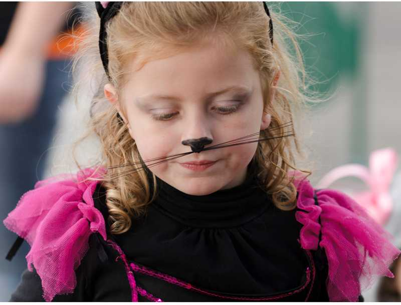 by: RAY HUGHEY - Serenity Peterson, 6,  decorated her nose with some kitty whiskers.