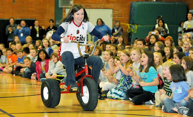 by: GARY ALLEN - Portland Trail Blazers mascot Blaze entertained students during a special assembly Friday afternoon at Mabel Rush Elementary School that also saw teacher Sarah Brown (above) participate in a tricycle race. The assembly was part of the Rip City Relay, a five-day tour through the state that delivered the official game ball to Portland's home opener Saturday. Gavin Russell received a t-shirt from Blaze, and fellow students Tyler Hardinger, Evie Palmer, Madelyn Morse, Reese Gutierrez, Saul Capell, Aidan Rodriguez, Sophia Carleton, Kyndra Davidson and Chris Davis were recognized by the school for displaying perseverance and excellence.