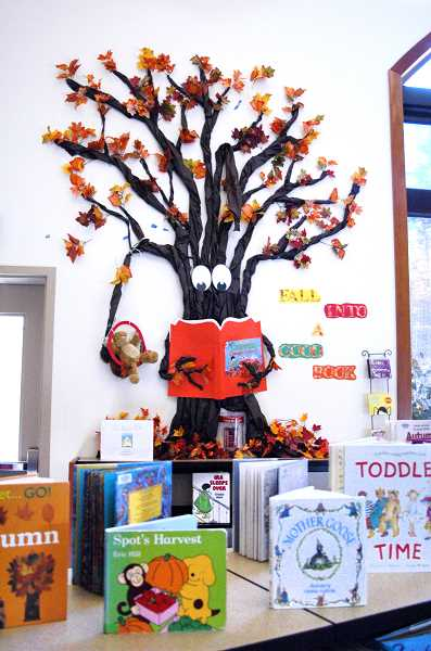 by: EISABEL GAUTSCHI - Laurie Bailey, who runs the Estacada Public Library's storytime hour, also creates many of the elaborate displays in the children's section of the library. This tree, believe it or not, has seasonal foliage. It is made mostly from recycled materials.