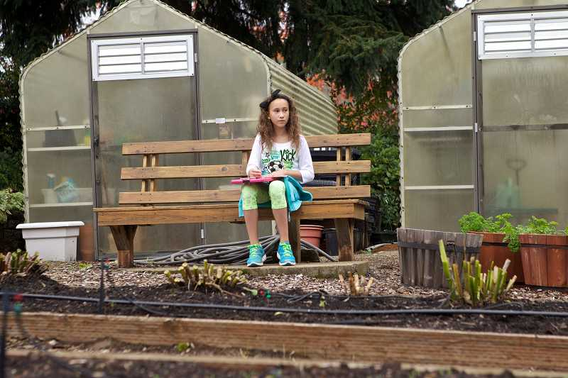 by: TIMES PHOTO: JAIME VALDEZ - Fifth-grader Bella Anderson writes journals about changes in the garden at Mary Woodward Elementary School. Her teacher Heather Miller uses the schools garden as part of her science curriculum.