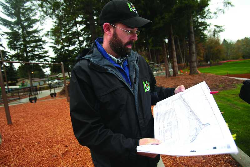 by: TIMES PHOTO: JONATHAN HOUSE - Gery Keck, A.M. Kennedy Park project planner with the Tualatin Hills Park and Recreation District, looks over the park's landscape plans now that the renovations are complete.