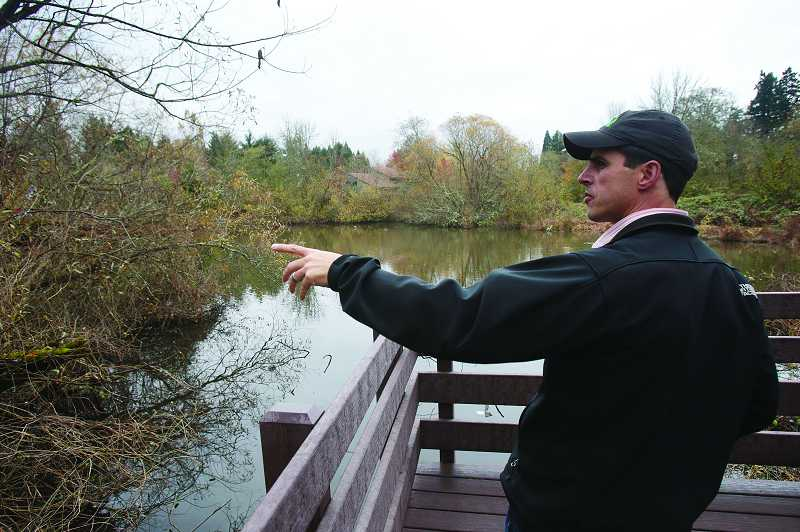 by: TIMES PHOTO: JONATHAN HOUSE - Tim Bonnin, Vista Brook park planner with the Tualatin Hills Park and Recreation District, discusses the landscape improvements to the park at its pond viewing area, which includes a boardwalk and platform.