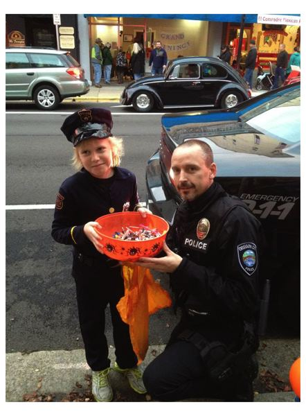 by: OCPD - Oregon City Reserve Officer Robert Libke is pictured distributing Halloween candy on Main Street just days before he was shot in the line of duty.