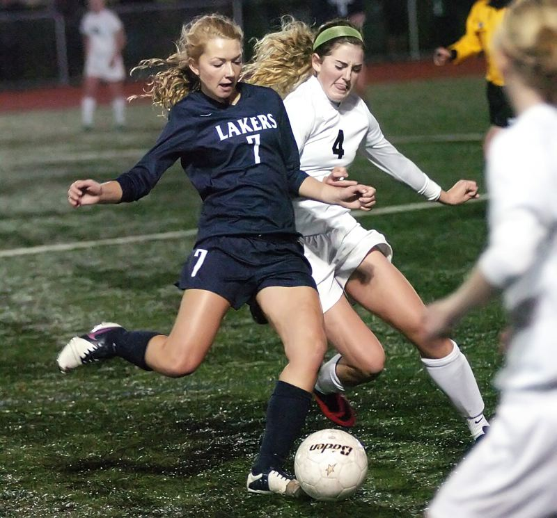 by: DAN BROOD - Lake Oswego's Lizzy Darling looks to clear a ball in the Lakers' opening-round playoff game against top-ranked Tigard.