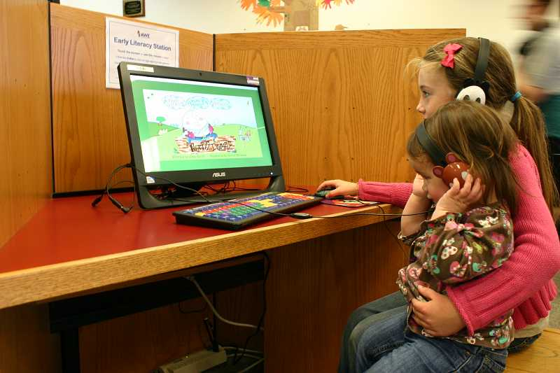 by: JASON CHANEY - Prineville eight-year-old Erica Bishop and her one-year old sister play an educational game at the computer station at Crook County Library. The computers were funded in part by a 2013 Facebook Community Action Grant.