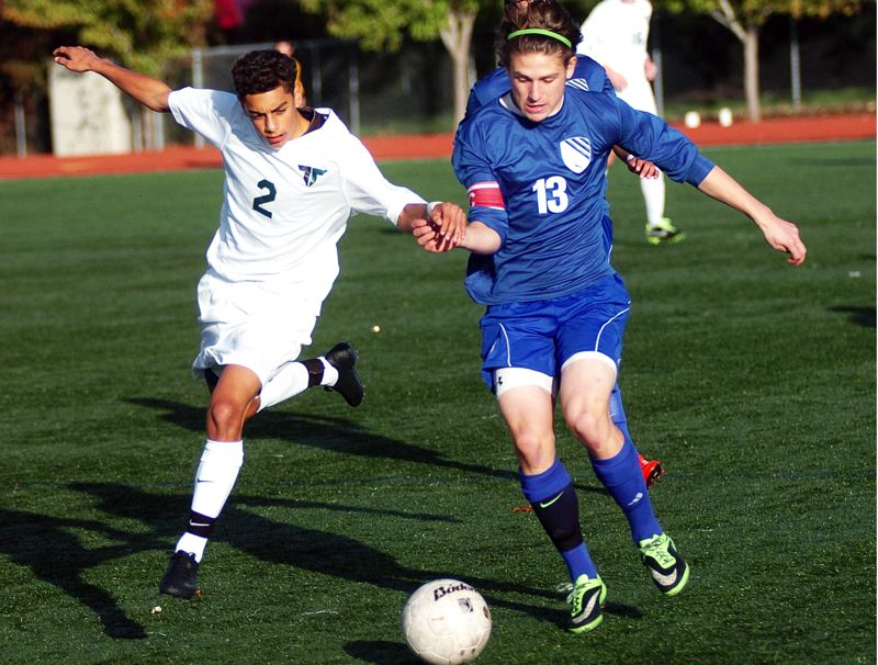 by: DAN BROOD - RACING -- Tigard junior Cesar Conteras (left) and South Medford senior Jeff Turner race to the ball during Saturday's state playoff match.