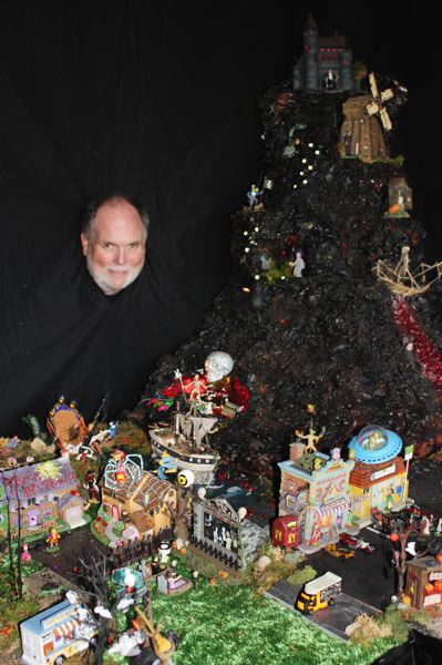 by: HILLSBORO TRIBUNE PHOTOS: DOUG BURKHARDT - LeFors peeks through a black curtain behind his elaborate miniature city, which he calls Tanisylvania.
