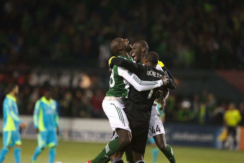 by: TRIBUNE PHOTO: JAIME VALDEZ - Portland Timbers defender Pa Modou Kah (center) and goalkeeper Donovan Ricketts (right) hug Pdefender Mamadou 'Futty' Danso after Danso scored the Timbers' third goal Thursday night against the Seattle Sounders.