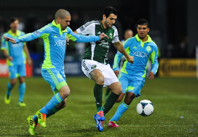 Diego Valeri (center) of Portland dribbles through the Seattle defense.